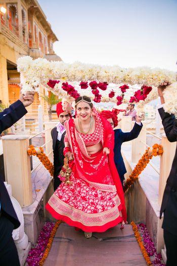Photo of Bride entering in benarasi red bridal lehenga