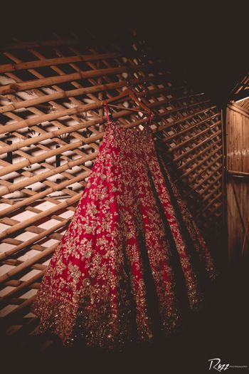 red and gold simple bridal lehenga on hanger