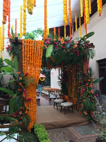 Entrance decor done with marigold garlands, lush greens and other flowers.
