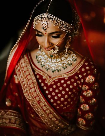A pictures of a bride in maroon lehenga and beautiful jewellery.