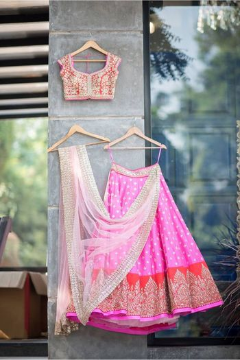 Photo of Light bridal lehenga on hanger in pink and red