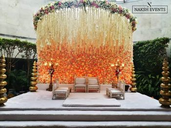 Mandap decor with an ombre floral wall and a huge floral chandelier.