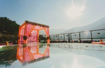 Photo of pink and orange theme pool-side mandap decor