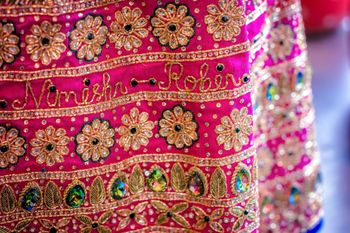 Bright pink lehenga with couple's names embroidered