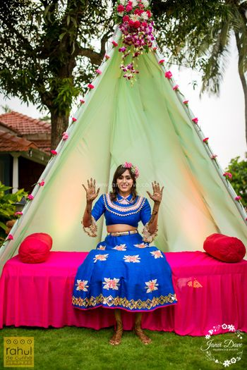 A bride in blue posing in front of a teepee tent on her mehndi