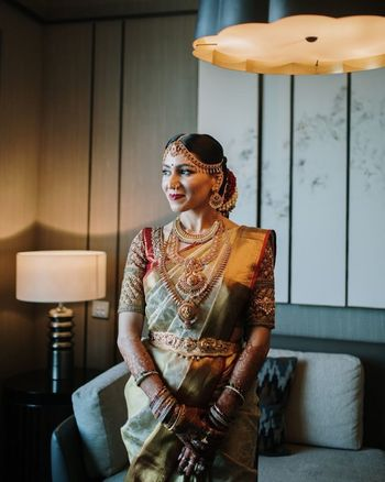 South Indian bride wearing a gold saree with an embellished blouse & temple jewellery.