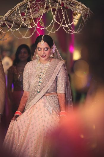 Photo of Bride in light grey and peach bridal lehenga