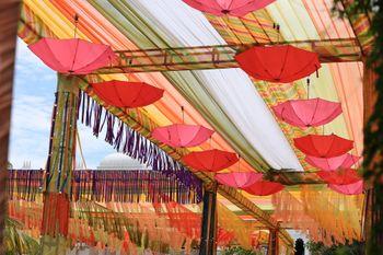 Mehendi decor idea with fringes and hanging umbrellas