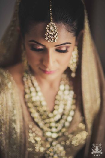 Bridal portrait with bride in gold makeup and lehenga