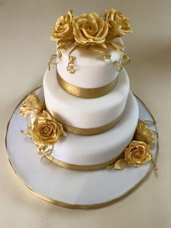3 tier white wedding cake with gold flowers