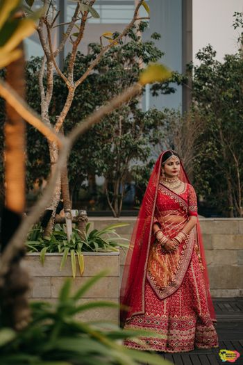 Photo of A bride in a red lehenga and a bandhani dupatta on her wedding