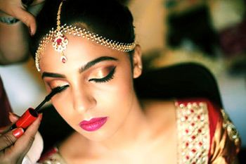 Bridal makeup with gold eyes and bright pink lips and mascara