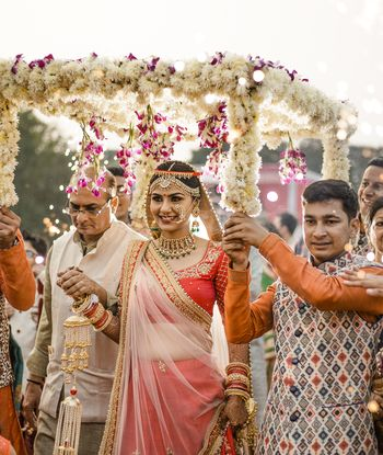 Bride entering under phoolon ki chadar in red lehenga