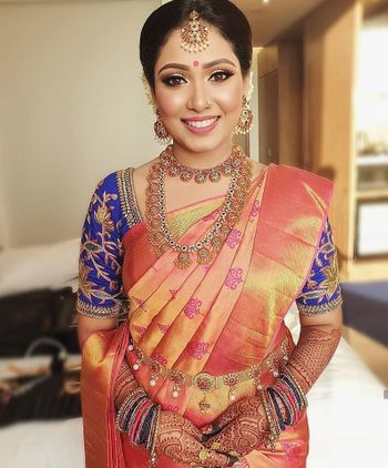 Southi Indian bride dressed in a coral saree with a navy blue blouse.