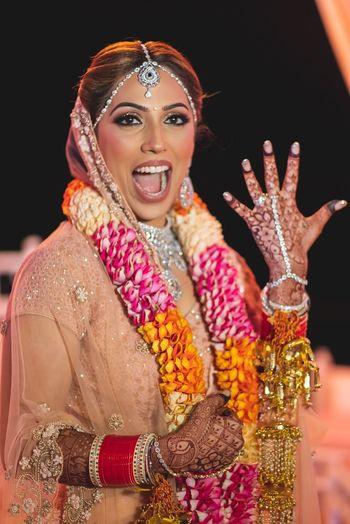 A bride in pink lehenga with unique jaimala