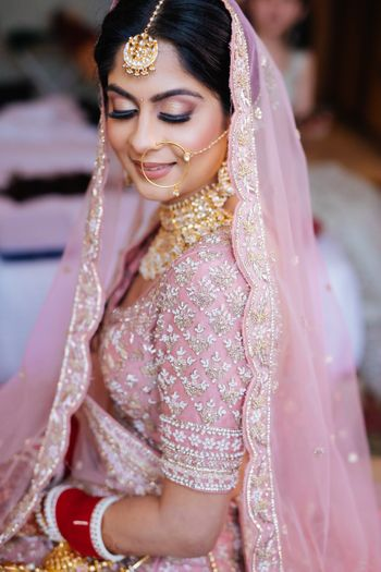Bride wearing pink lehenga with contrasting jewellery.
