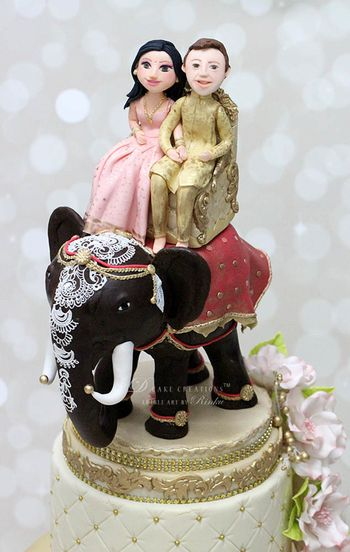 Photo of Destination wedding cake topper with couple on elephant