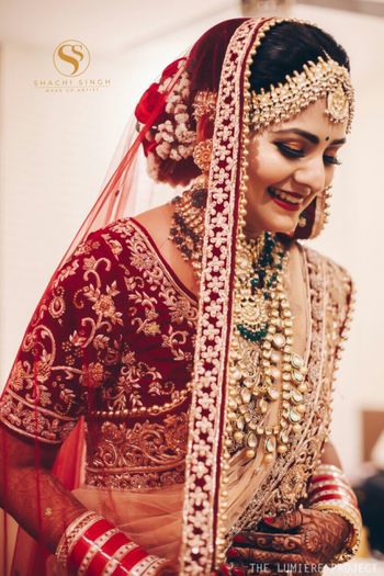 Gorgeous bride wearing maroon blouse with polki and emeralds jewelry