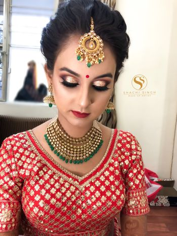 Pretty bride in red embroidered blouse with gold jewelry
