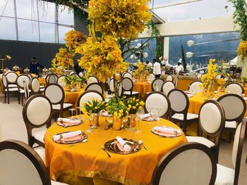 Table settings done with yellow table spreads and wooden chairs.
