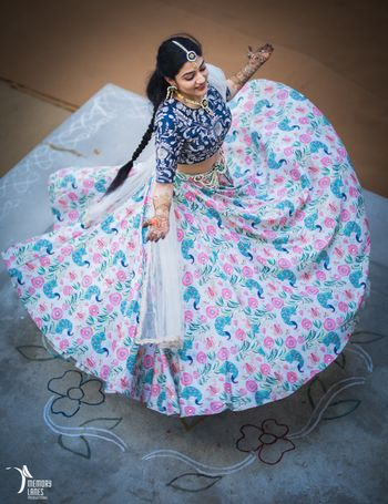 Photo of Bride twirling in offbeat white and blue floral print lehenga