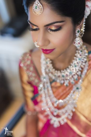 South Indian bride with gold eyes and emerald and diamond jewellery