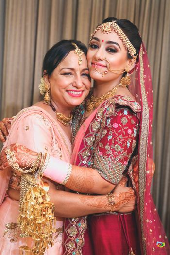 A bride in a red lehenga posing with her mother