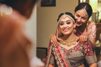 A bride all dolled up for the day, posing with her mother
