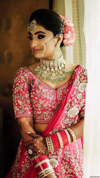 Bride in blush pink lehenga and exquisite jewellery.