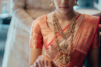 Photo of A South Indian bride wearing a layered temple jewellery necklace.