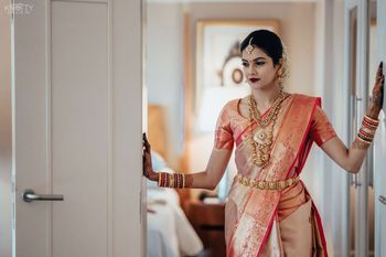 Photo of South Indian bride wearing a dual toned silk saree with temple jewellery.
