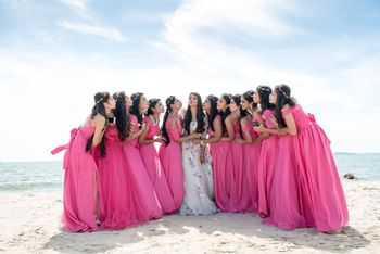 Coordinated bridesmaids in pink with bride on beach