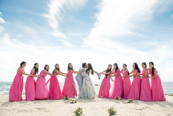 Couple kissing with matching bridesmaids in beach wedding