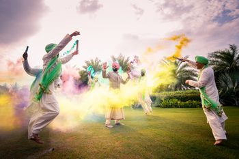 Photo of A group of groomsmen dancing with smoke bombs with the groom in the centre.