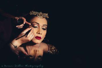 Bride getting makeup done with deep maroon lipstick
