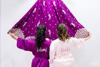 Bride with bridesmaid getting ready in robe
