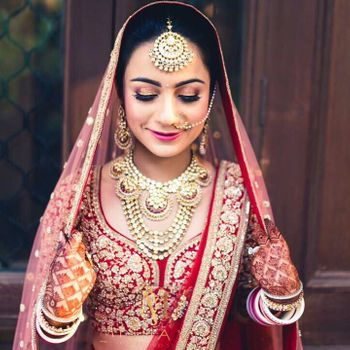 Bride in red acting shy holding dupatta