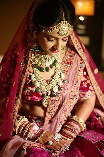 Contrasting layered bridal jewellery with red lehenga