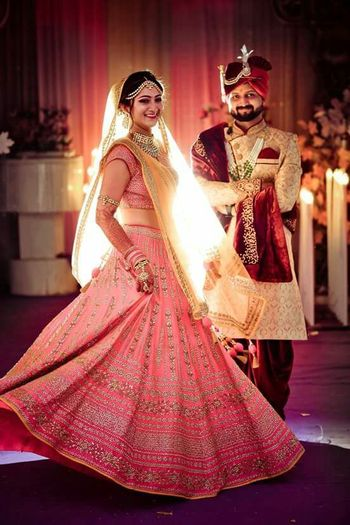 Cute twirling bridal shot with a baby pink lehenga