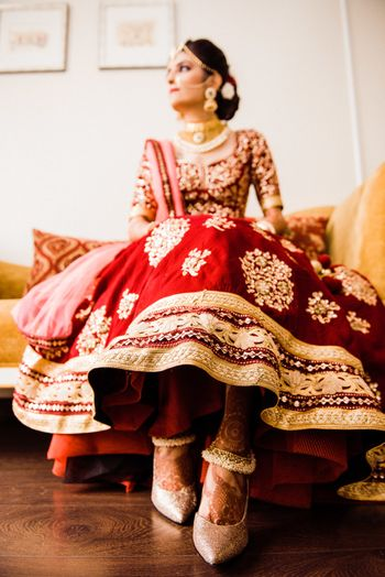 wedding day bridal portrait with bride showing off lehenga and shoes
