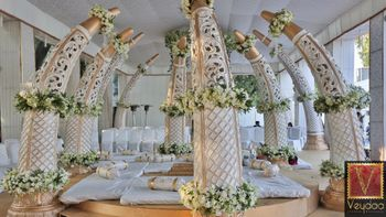 Photo of White and gold ivory tusk shaped mandap