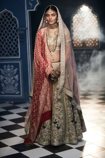 A bride in a dull gold lehenga with a contrasting Benarasi dupatta