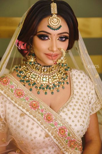 A bride in peach outfit and unique jewellery