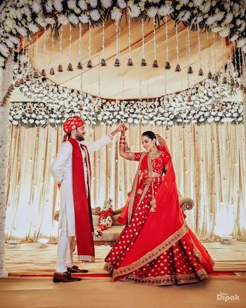 The bride is stunning red lehenga dancing with the groom
