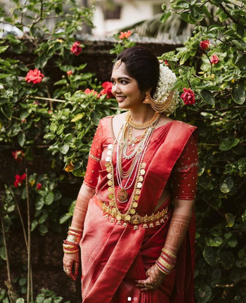 South Indian bride in a brick red saree with contrasting jewellery.
