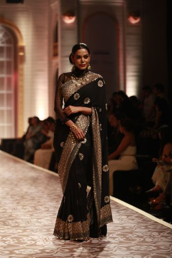 Photo of Elegant black saree with large border  and full sleeves high neck blouse