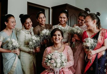 Bride with her bridesmaids holding the bouquet.