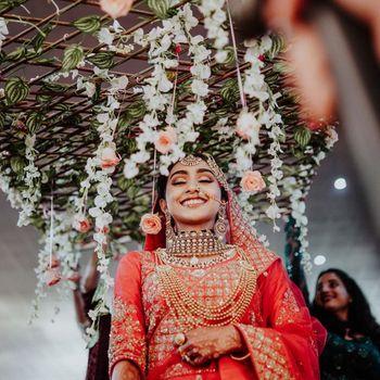 Photo of A happy bride under phoolon ki chadar.