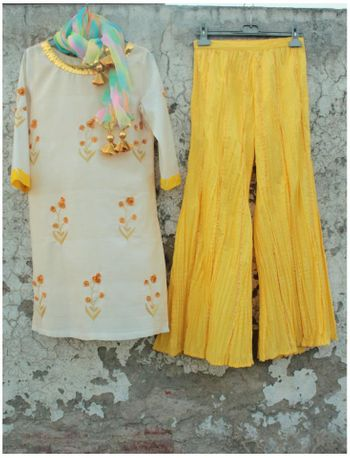 Photo of wide legged pallazo pants in yellow with white kurta and gota work. tie dye dupatta