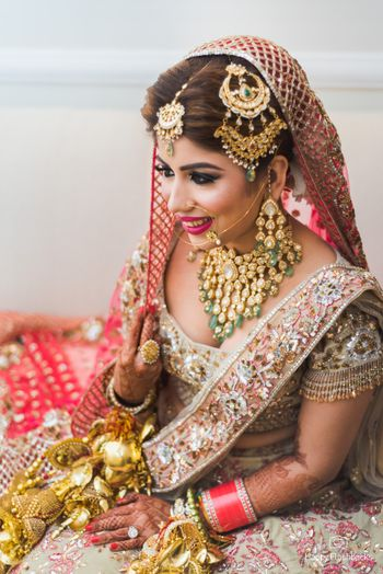 Bridal pose with heavy bridal jewellery and beautiful jhoomer